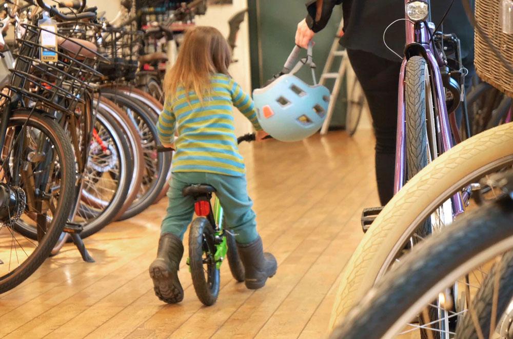 Barn som lär sig cykla på en balanscykel i en Sportsonbutik
